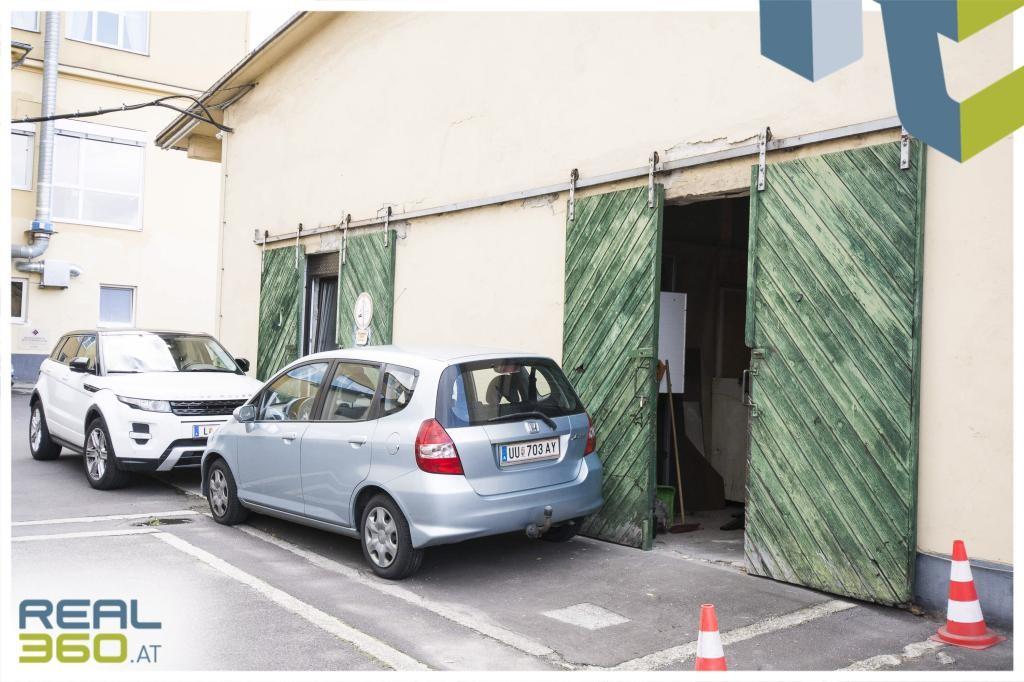 Einfahrtstor mit Parkplätze davor