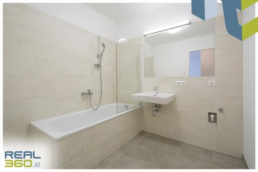 Badezimmer mit Badewanne und Duschwand